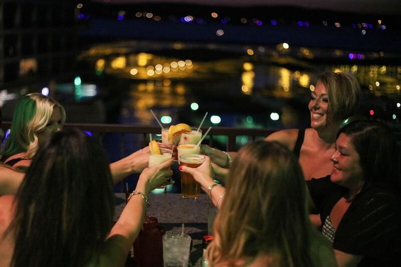 women raising glasses on deck at night at camden on the lake