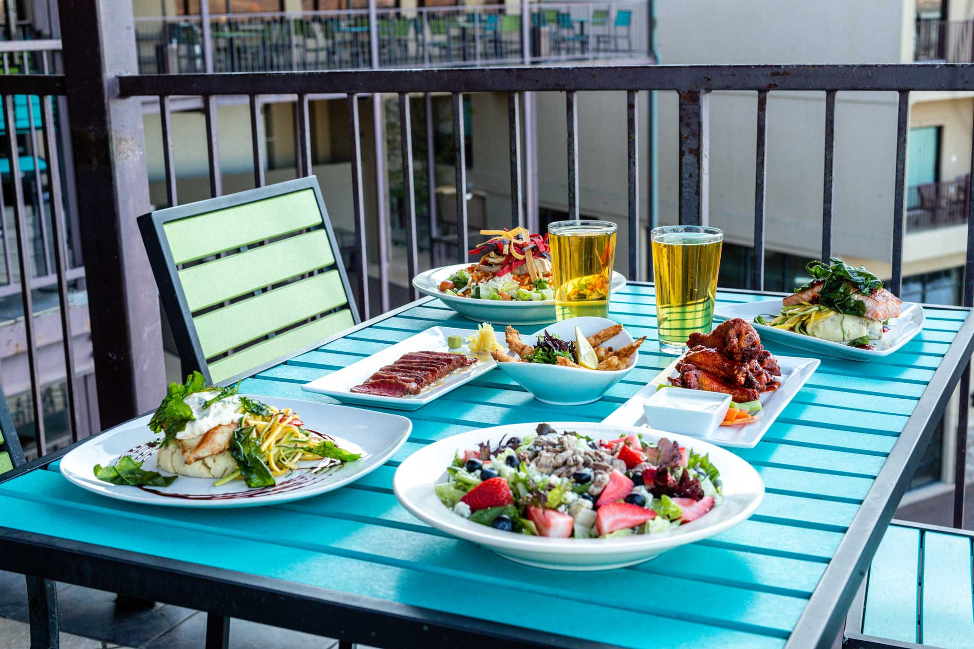 entrees and appetizers on a blue table with pints of beer - outdoor dining at camden on the lake