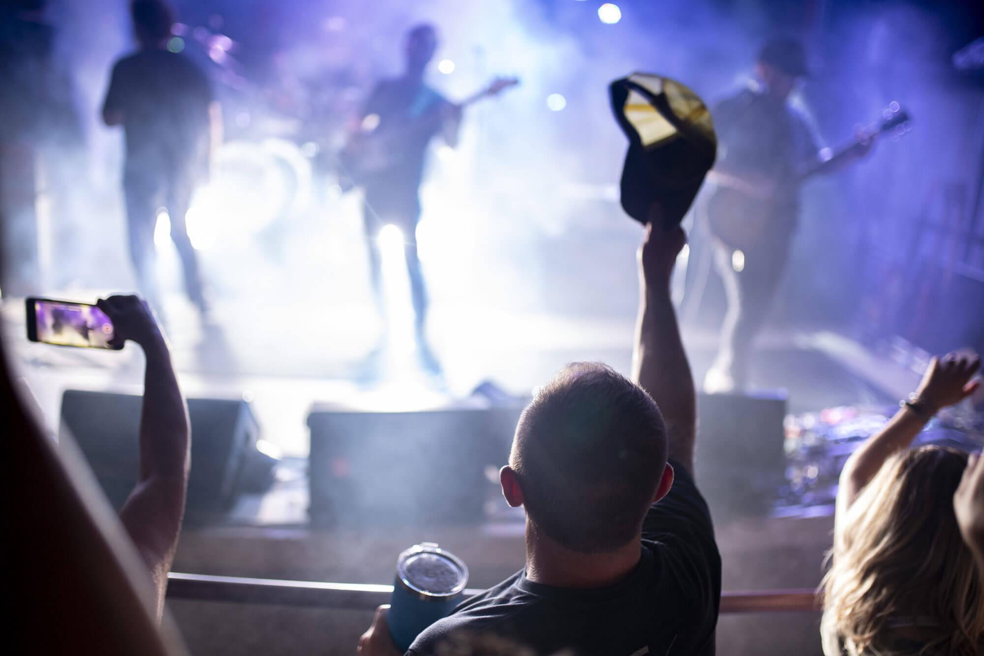 man waving hat at concert at horny toads