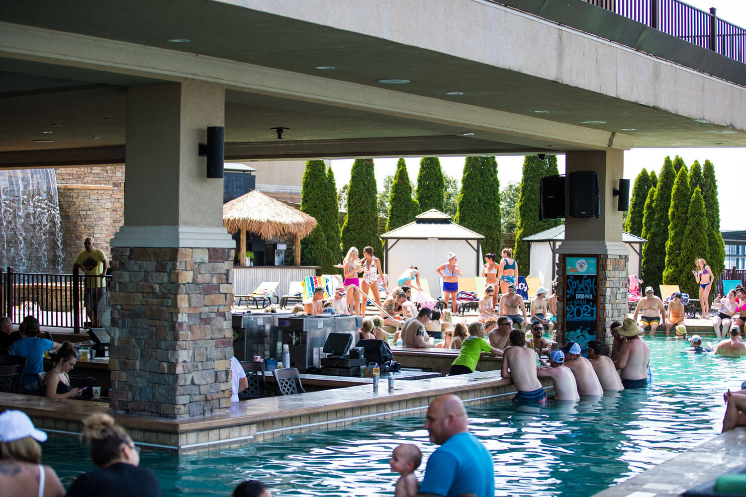 An outdoor bar and pool with swim up bar at camden on the lake