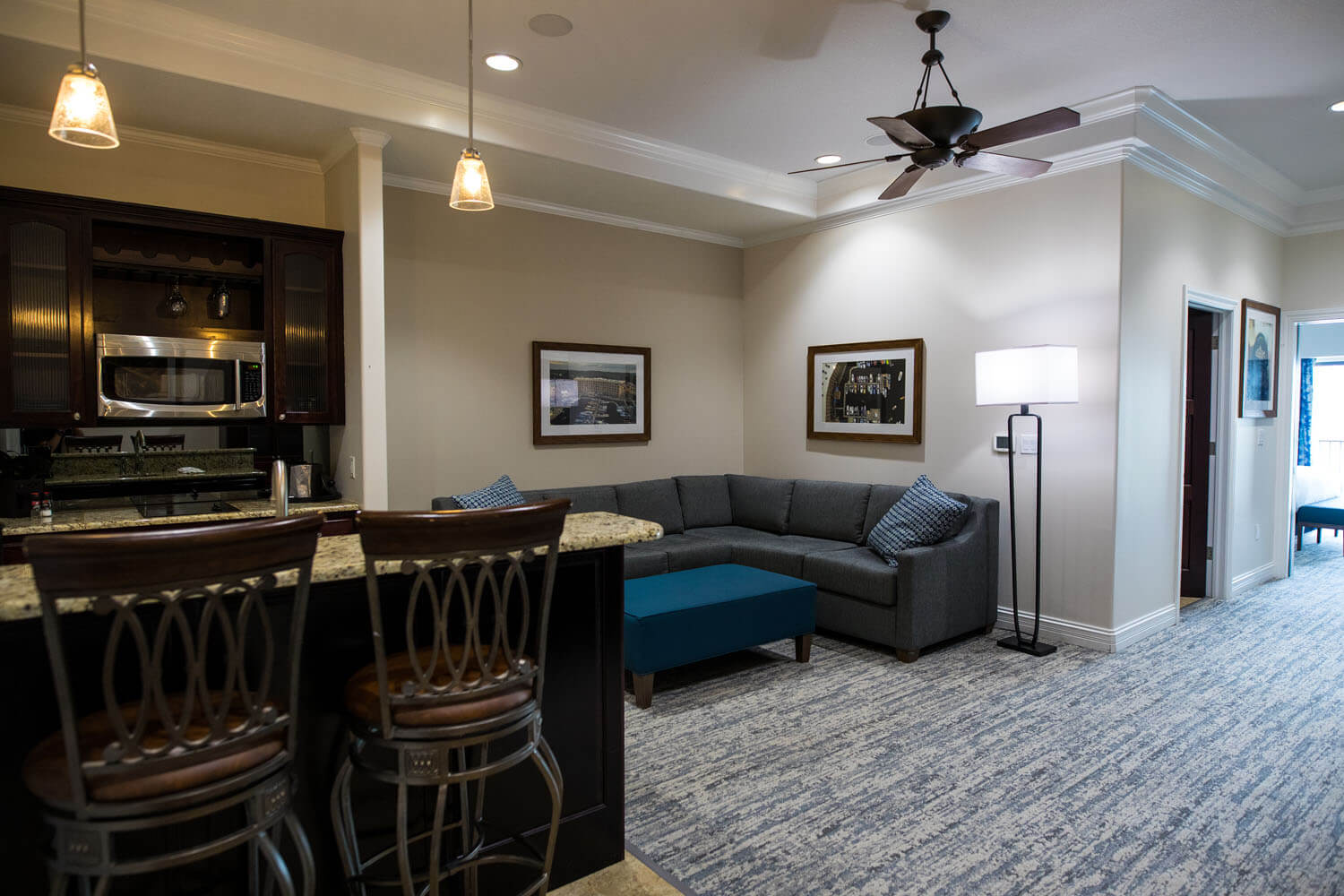 Living space featuring kitchenette seating, couch, and wall decor in suite at Camden on the Lake Resort Lake of the Ozarks