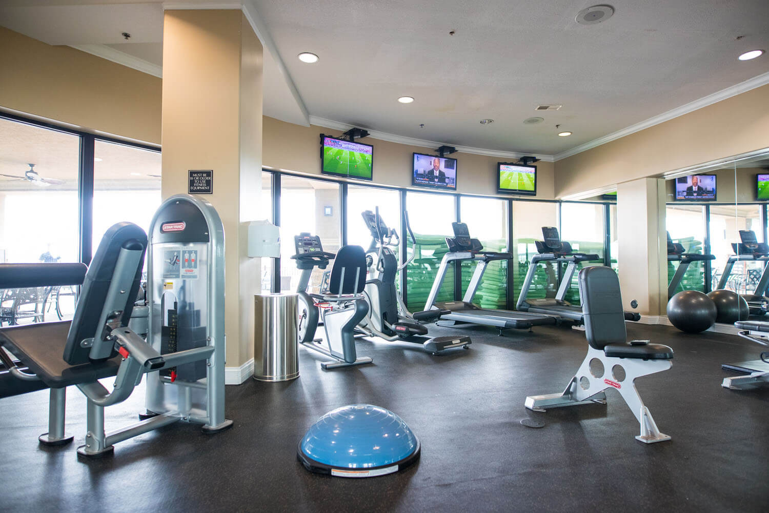 Fitness room at Camden on the Lake resort featuring exercise and cardio machines and televisions