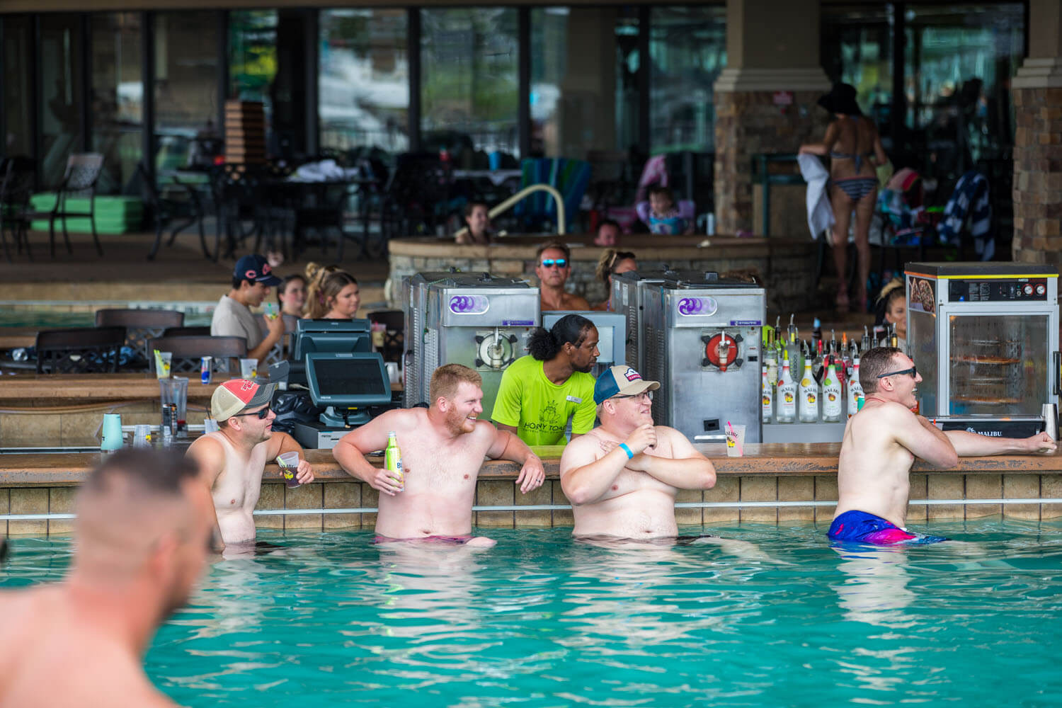 A group seated at the swim up bar in the pool at Camden on the Lake Resort