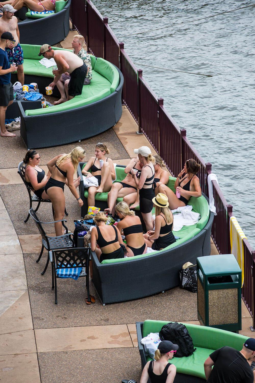 a group of women enjoying waterfront patio seating at camden on the lake resort