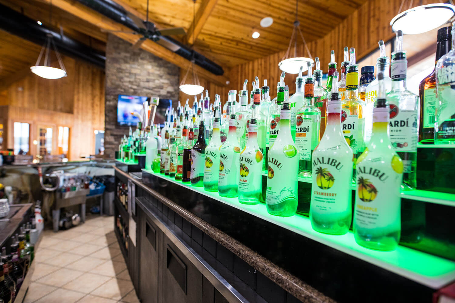 Shelves filled with alcohol bottles, featuring flavored Malibu rums in the front at Toad Island Bar & Grill Camden on the Lake